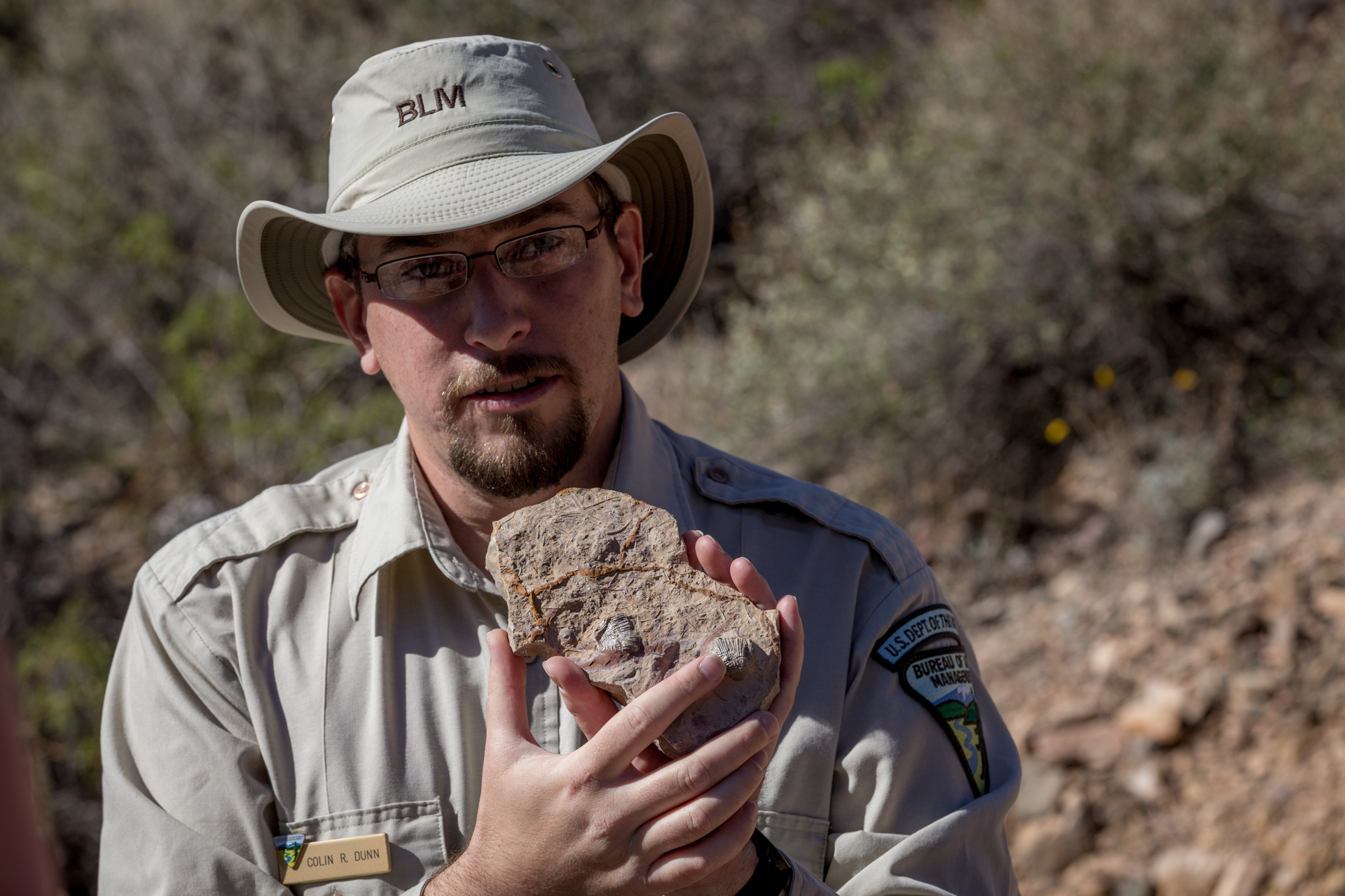 Colin Dunn, paleontologist with the Bureau of Land Management, shows us a rock loaded with fossils.
